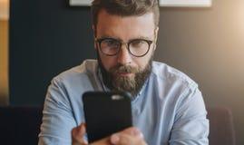 Porträt des jungen bärtigen attraktiven Geschäftsmannes im Hemd und in den Gläsern unter Verwendung des Smartphone, arbeitend Hip Stockbild