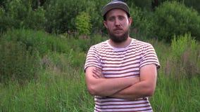 Porträt des jungen bärtigen lustigen Mannes mit den Kappenquerhänden stock video