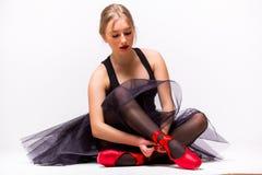 Porträt des jungen Ballerinaballetttänzers, der Pantoffel um ihre Beine bindet Stockbild