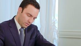 Porträt des jungen behinderten Geschäftsmannes, saffered von Krankheit Parkinson s, sitzend in einem Bürostuhl und tun Schreibarb stock video