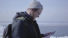 Porträt des jungen blonden bärtigen gut aussehenden Mannes, der warme Jacke und den Hut geht auf den Gletscher überprüft mit der  stock video footage