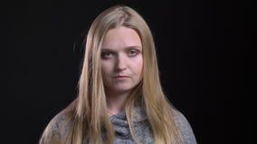 Porträt des jungen blonden gerad-haarigen Mädchens, das ernsthaft in Kamera auf schwarzem Hintergrund aufpasst stock video footage