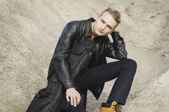 Porträt des jungen blonden Gitarristen, der auf Sand sitzt Lizenzfreies Stockbild