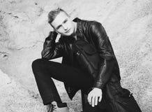 Porträt des jungen blonden Gitarristen, der auf Sand sitzt Lizenzfreie Stockfotografie
