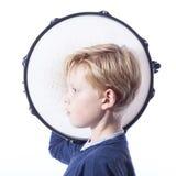 Porträt des jungen blonden Jungen mit Trommel gegen weißen Hintergrund Lizenzfreies Stockbild