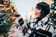 Porträt des jungen Brunette nahe gemaltem Weihnachtsbaum auf Straße stockfotografie