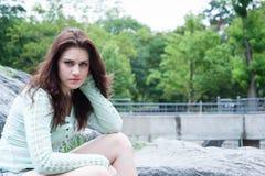 Porträt des jungen Brunette sitzend auf den bouders Stockfoto