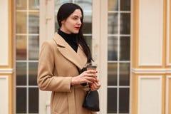 Porträt des jungen brunette trinkenden Kaffees, Wartefreund in der Stadt Tragender eleganter Mantel mit der kleinen schwarzen Han stockfotografie