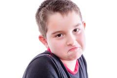 Porträt des Jungen die Stirn runzelnd im weißen Studio Stockfotografie