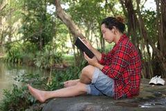 Porträt des jungen entspannten Mannes im roten Hemd ein Buch im schönen Naturhintergrund lesend Lizenzfreies Stockfoto
