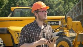 Porträt des jungen Erbauers im Sturzhelm, der die Tablette und Die Stirn runzeln, vorwärts schauend hält, durchdacht, Traktor auf stock video footage