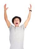 Porträt des jungen erfolgreichen Mannes, der oben ihm Hände zujubelt und aufzieht Lizenzfreie Stockfotos