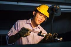 Porträt des jungen Erwachsenen erfuhr industrielle asiatische Arbeitskraft über Industriemaschinerie Stockfoto