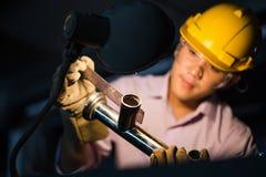 Porträt des jungen Erwachsenen erfuhr industrielle asiatische Arbeitskraft über Industriemaschinerie Stockfotografie