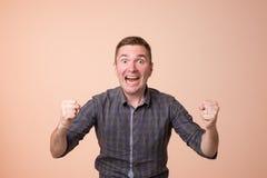 Porträt des jungen europäischen Mannes mit entsetztem Gesichtsausdruck Er kann seinem Glück oder Erfolg nicht glauben Stockbilder