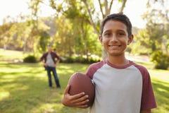 Porträt des Jungen Fußball im Park, Vati halten im Hintergrund lizenzfreie stockfotografie
