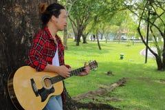 Porträt des jungen Gitarristen stehend gegen einen Baum und Akustikgitarre im schönen Naturhintergrund spielend Stockbild