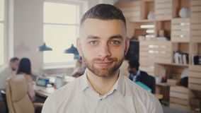 Porträt des jungen glücklichen kaukasischen Geschäftsmannes, der im beschäftigten Büro aufwirft Hübsche männliche kreative Arbeit stock video