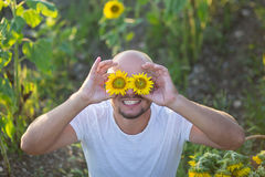 Porträt des jungen glücklichen Mannes, der auf einem Sonnenblumenfeld lächelt und sitzt Stockfoto
