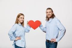 Porträt des jungen glücklichen Paars in der Liebe, die rotes Papierherz hält Lizenzfreies Stockfoto