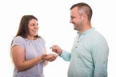 Porträt des jungen glücklichen Paars Hausschlüssel gebend Lizenzfreie Stockfotografie