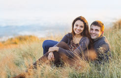 Porträt des jungen glücklichen Paars lachend an einem kalten Tag durch das Meer Stockfotografie