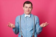 Porträt des jungen gut aussehenden Mannes mit erstauntem Gesichtsausdruck, shruggs Schultern mit dem Zögern, herein gekleidet im  lizenzfreie stockfotografie