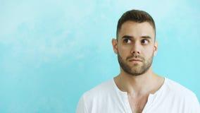 Porträt des jungen gutaussehenden Mannes Gesicht verziehendes in Kamera und in verschiedene Gefühle der Show auf blauem Hintergru Stockbild