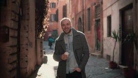 Porträt des jungen gutaussehenden Mannes Kamera betrachtend Glücklicher lächelnder Mann, der in der Morgenstraße, trinkender Kaff Stockfoto