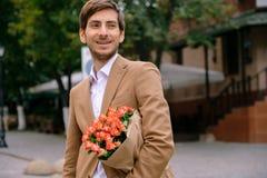 Porträt des jungen gutaussehenden Mannes lächelnd, ein Bündel Rosen halten Stockfotos