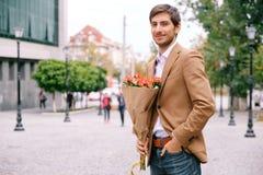 Porträt des jungen gutaussehenden Mannes lächelnd, ein Bündel Rosen halten Lizenzfreies Stockfoto