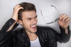 Porträt des jungen gutaussehenden Mannes Sonnenbrille halten stockbilder