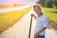 Porträt des Jungen hält den Griff eines Koffers im sonnigen DA Lizenzfreies Stockbild