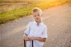 Porträt des Jungen hält den Griff eines Koffers im sonnigen DA Lizenzfreie Stockfotografie