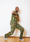 Porträt des jungen hübschen afrikanischen Mannes, der das lächelnde Gestikulieren des hellgrünen nationalen Kostüms trägt Stockfotografie