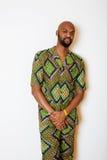Porträt des jungen hübschen afrikanischen Mannes, der das lächelnde Gestikulieren des hellgrünen nationalen Kostüms trägt Stockbild