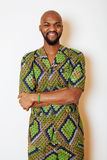 Porträt des jungen hübschen afrikanischen Mannes, der das lächelnde Gestikulieren des hellgrünen nationalen Kostüms trägt Lizenzfreies Stockbild