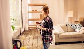 Porträt des jungen hübschen Mädchens, das durch das Fenster hält Tasse Tee oder Kaffee schaut lizenzfreies stockbild