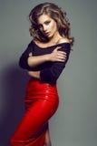Porträt des jungen hübschen Modells mit dem langen gewellten Haar, das schwarze Spitze und roten Lederrock trägt stockbilder