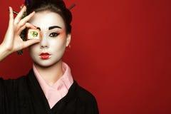 Porträt des jungen heisha im Kimono, der ein Stück Sushi vor ihrem Auge auf rotem Hintergrund hält lizenzfreies stockfoto