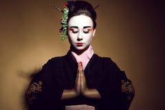Porträt des jungen heisha im Kimono, der mit den traditionellen gefalteten Händen begrüßt lizenzfreie stockfotografie