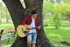 Porträt des jungen Hippie-Kerls, der gegen einen Baum steht und Akustikgitarre im schönen Naturhintergrund spielt Lizenzfreies Stockbild