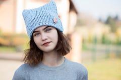 Porträt des jungen Hippie-Mädchens in der grauen Wollkappe stockfotografie