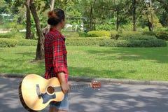Porträt des jungen Hippie-Mannes, der Akustikgitarre in der Natur mit Kopienraumhintergrund hält Lizenzfreie Stockfotos
