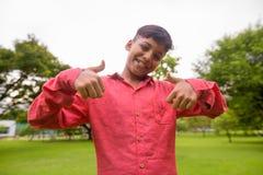 Porträt des jungen indischen Jungen, der am Park sich entspannt stockfotografie