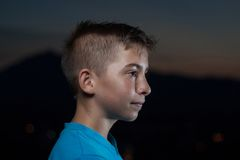 Porträt des jungen Jugendlichen in einer Berglandschaft in der Dämmerungszeit Stockbild
