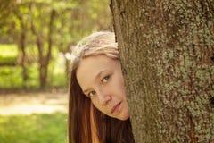 Porträt des jungen Jugendlichmädchens, das hinter Baum sich versteckt Stockbilder