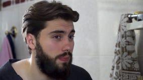 Porträt des jungen Jugendlichmannes, der in einem Hauptbadezimmerspiegel tut sein Haar und wird fertig in betrachtet stock footage