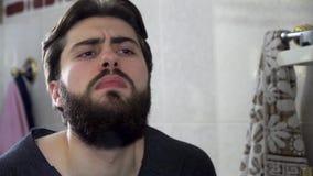 Porträt des jungen Jugendlichmannes, der in einem Hauptbadezimmerspiegel tut sein Haar und wird fertig in betrachtet stock video