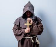 Porträt des jungen katholischen Mönchs mit Kreuz Stockfotografie